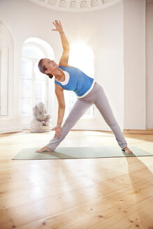 Woman in extended triangle pose in sunny yoga studio - MFF003217