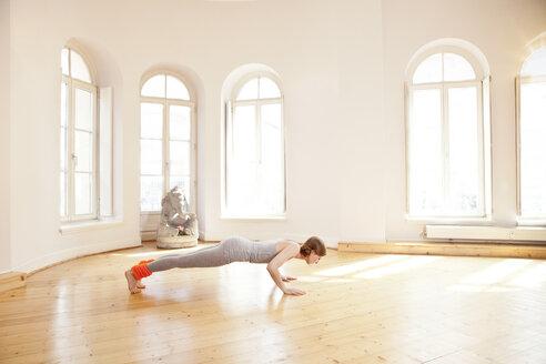 Woman in sunny yoga studio holding Chaturanga Dandasana pose - MFF003253