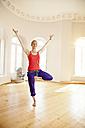 Happy woman in sunny yoga studio holding tree pose - MFF003256