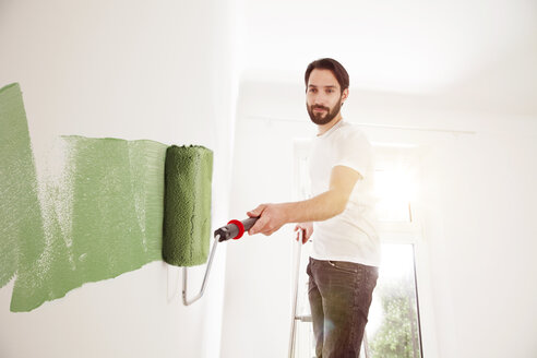 Young man painting a wall green - MFF003271