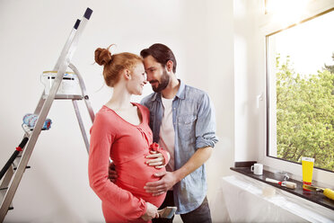 Happy man hugging pregnant woman while renovating new home - MFF003274