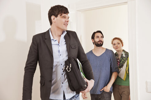 Real estate agent showing a couple around in a new apartment - MFF003280