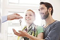 Young couple receiving house key from real estate agent - MFF003286