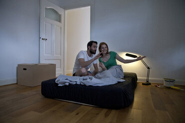 Young couple spending the first night in their new apartment making plans - MFF003292
