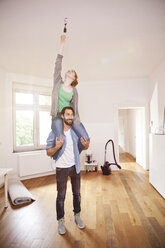 Young couple exchanging a light bulb in their new apartment together - MFF003295