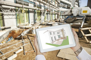 Hands holding a digital tablet with an architectural house sketch in front of a contruction site - MFF003298