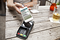 Hand with smart phone mobile paying at a cafe - MFF003301