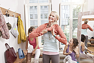 Woman putting on her clothes in yoga studio changing room - MFF003310