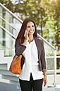 Smiling woman on cell phone outdoors - MFF003334