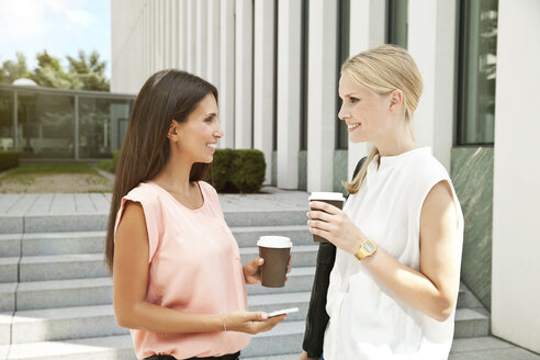 Two businesswomen talking outside during a coffee break - MFF003337