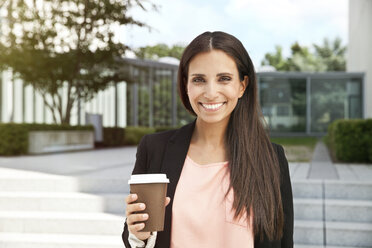 Portrait of smiling woman holding takeaway coffee outdoors - MFF003340