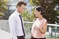 Smiling businesswoman and businessman talking outdoors - MFF003343