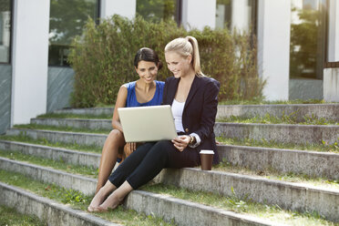 Two businesswomen sitting on stairs outside using a laptop - MFF003346