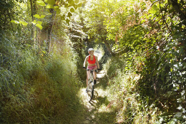 Young woman riding mountainbike on a trail - MFF003349