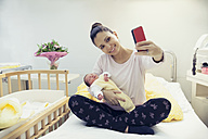 Mother taking a selfie with her newborn baby in hospital bed - MFF003361