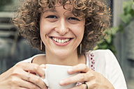 Portrait of smiling young woman with cup of coffee - TAMF000635