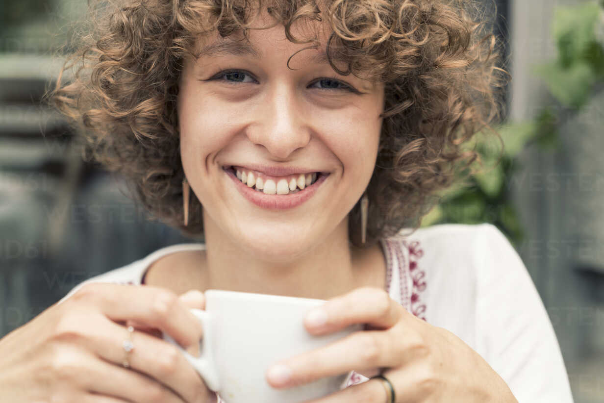 Portrait of smiling young woman with cup of coffee - TAMF000635 - A. Tamboly/Westend61