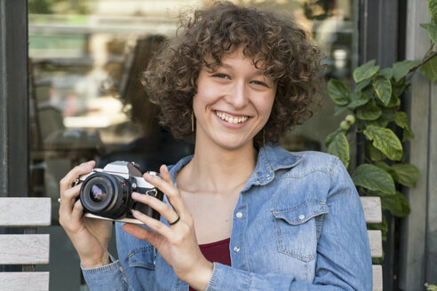 Portrait of smiling young woman with old camera sitting in a sidewalk cafe - TAMF000638