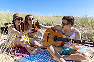 Friends toasting with beer bottles on the beach - MGOF002363