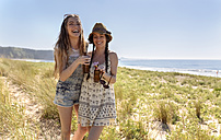 Two friends with beer bottles relaxing on the beach - MGOF002372