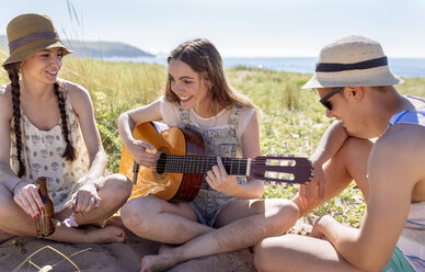 Smiling teenage girl playing guitar for her friends on the beach - MGOF002378