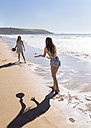Two women playing beach paddles on the beach - MGOF002381