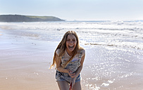 Laughing teenage girl on the beach - MGOF002384
