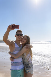 Young couple in love taking selfies on the beach - MGOF002396
