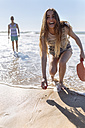 Laughing teenage girl playing beach paddles on the beach - MGOF002399