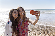 Two best friends taking selfie with smartphone on the beach - MGOF002402