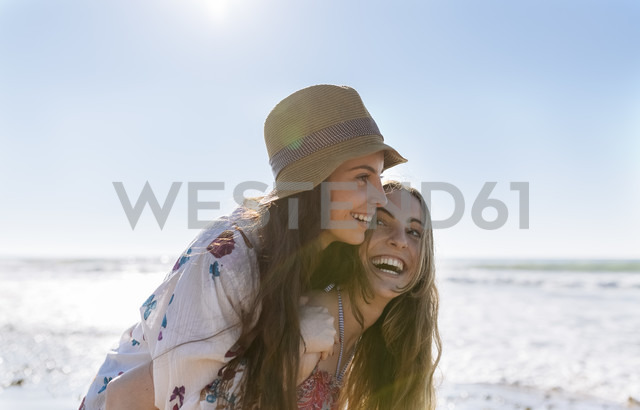 Teenage girl giving her best friend a piggyback ride on the beach - MGOF002405 - Marco Govel/Westend61