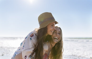 Teenage girl giving her best friend a piggyback ride on the beach - MGOF002405