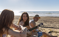 Three friends relaxing together on the beach - MGOF002420