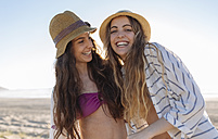 Portrait of two best friends wearing hats on the beach - MGOF002429