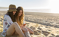 Two best friends sitting on the beach looking at smartphone - MGOF002432