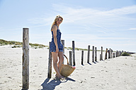 Young woman waiting at wooden poles on the beach - SRYF000023