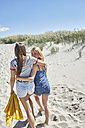 Two female friends walking arm in arm on the beach - SRYF000029