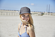 Happy young woman wearing baseball cap on the beach - SRYF000047
