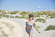 Happy young woman on the beach playing beach paddles - SRYF000050