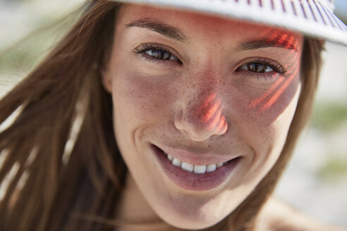 Portrait of smiling young woman wearing sun visor - SRYF000056