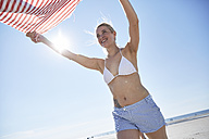 Young woman lifting towel on the beach - SRYF000071