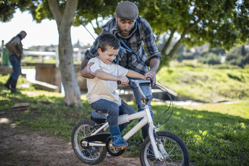 Father supporting son on bike - ZEF010212