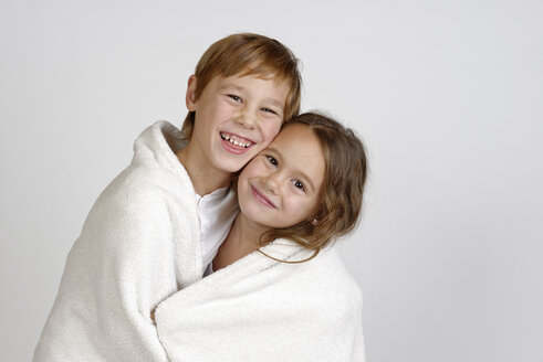 Portrait of laughing boy sharing blanket with his little sister - LBF001462