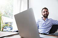 Young man with laptop at the window - WESTF021649