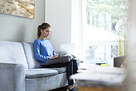Young woman sitting on couch using laptop - WESTF021694