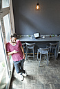 Young man in a cafe using cell phone - WESTF021706