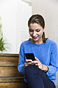 Young woman sitting on stairs looking at smartphone - WESTF021712