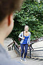 Smiling young woman walking up stairs in park - WESTF021733