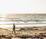 France, Crozon peninsula, woman walking on beach at sunset - UUF008327