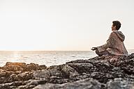 France, Crozon peninsula, woman meditating at beach at sunset - UUF008339